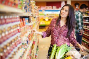 mujer caminando por pasillo en supermercado, buscando productos.